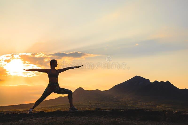 Het silhouet van jonge vrouw het praktizeren yoga of pilates bij zonsondergang of zonsopgang in mooie bergplaats, het doen valt u royalty-vrije stock foto's