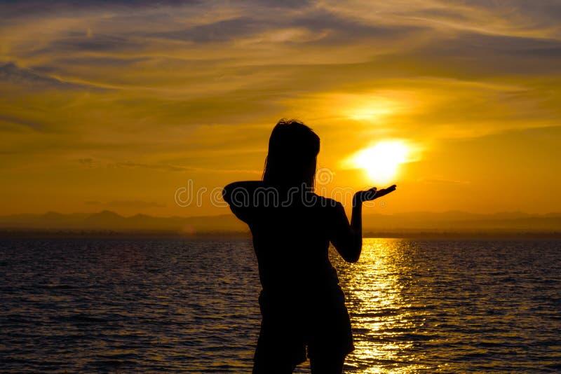 Het silhouet van Langharige vrouwen bevindende Handen omhoog om de zonsondergang te krijgen royalty-vrije stock foto