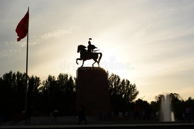 Het silhouet van het Manasstandbeeld bij zonsondergang Ala ook vierkant bishkek kyrgyzstan royalty-vrije stock fotografie