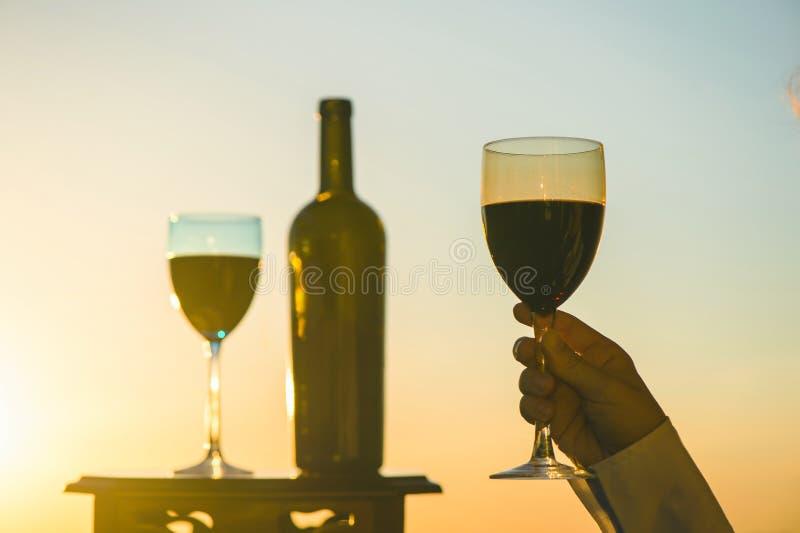 Het silhouet van mannetje en wijfje overhandigt roosterende wijn op zonsondergangachtergrond royalty-vrije stock afbeelding