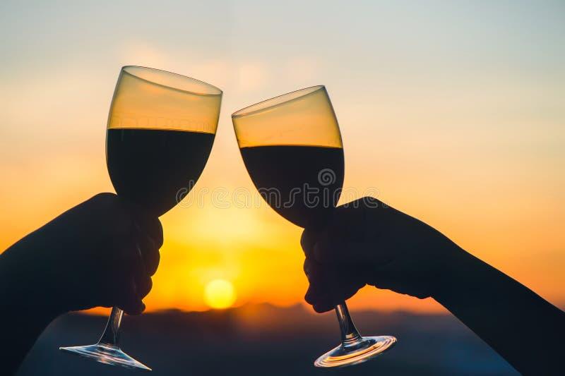 Het silhouet van mannetje en wijfje overhandigt roosterende wijn op zonsondergangachtergrond royalty-vrije stock afbeeldingen