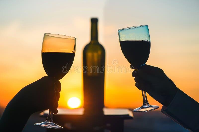 Het silhouet van mannetje en wijfje overhandigt roosterende wijn op zonsondergangachtergrond royalty-vrije stock foto's
