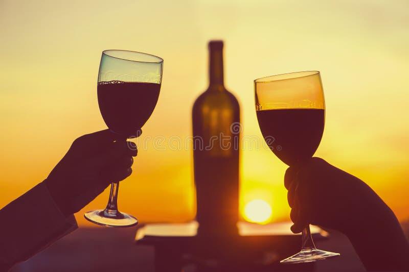Het silhouet van mannetje en wijfje overhandigt roosterende wijn op zonsondergangachtergrond Het romantische paar vieren bij een  stock afbeelding