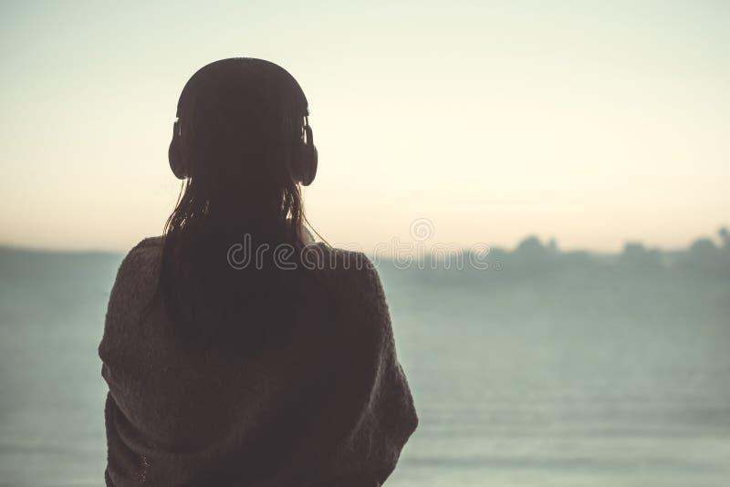 Het silhouet van naakte vrouw met nat haar verpakte in een deken na het zwemmen royalty-vrije stock foto