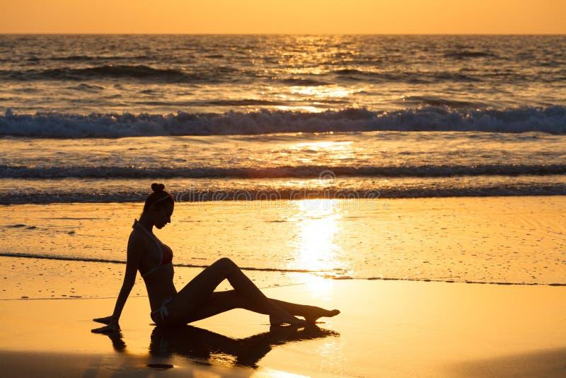 Het silhouet van ontspant meisje op het strand bij zonsondergang Vrouw op achtergrond van de oceaan royalty-vrije stock afbeelding