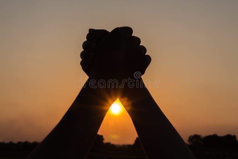 het silhouet van paarholding overhandigt op het vieren overwinningsbeauti stock afbeelding