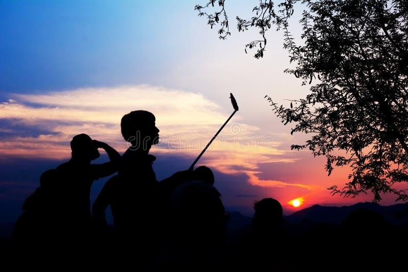 Het silhouet van Reizigers geniet van Hun Ogenblik het Letten op Zonsondergang stock fotografie