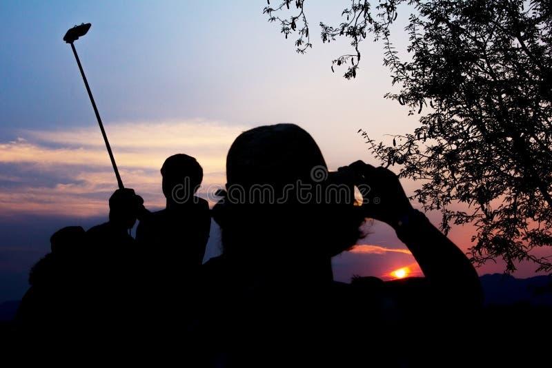 Het silhouet van Reizigers geniet van Hun Ogenblik het Letten op Zonsondergang stock foto