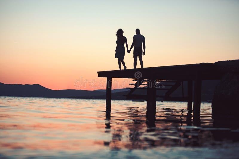 Het silhouet van het schemerpaar op pijler op zee water het silhouetgang van het schemerpaar bij zonsondergang overzeese toevluch stock afbeeldingen