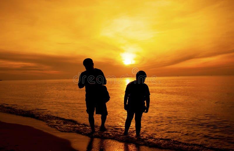 Het silhouet van Vader en zoon nam een gang op het strand stock afbeeldingen