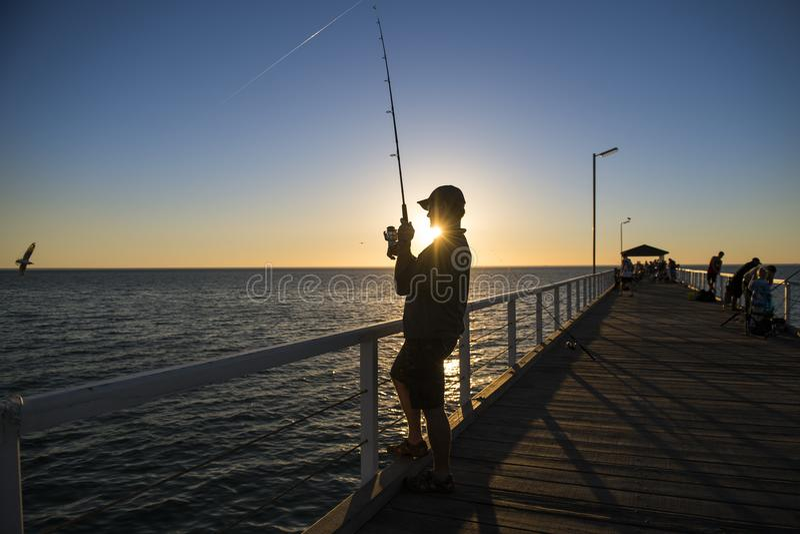 Het silhouet van visser met hoed en vissenstaaf die zich op overzees dok bevinden die bij zonsondergang met mooie oranje hemel in royalty-vrije stock afbeeldingen