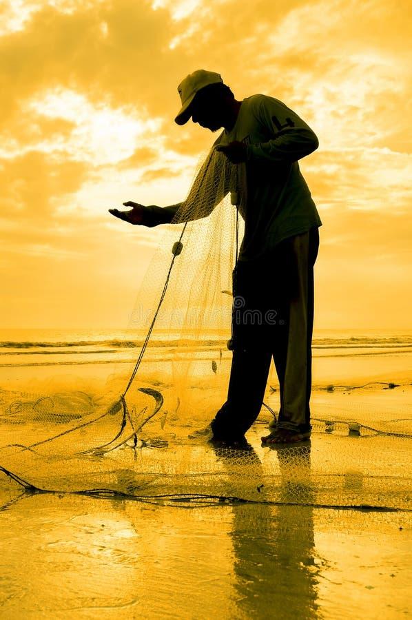 Het silhouet van vissers herstelt zijn netto royalty-vrije stock foto