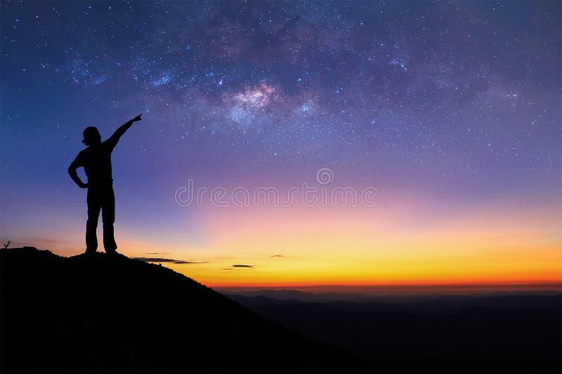 Het silhouet van vrouw bevindt zich bovenop berg en richt aan de melkachtige manier stock fotografie