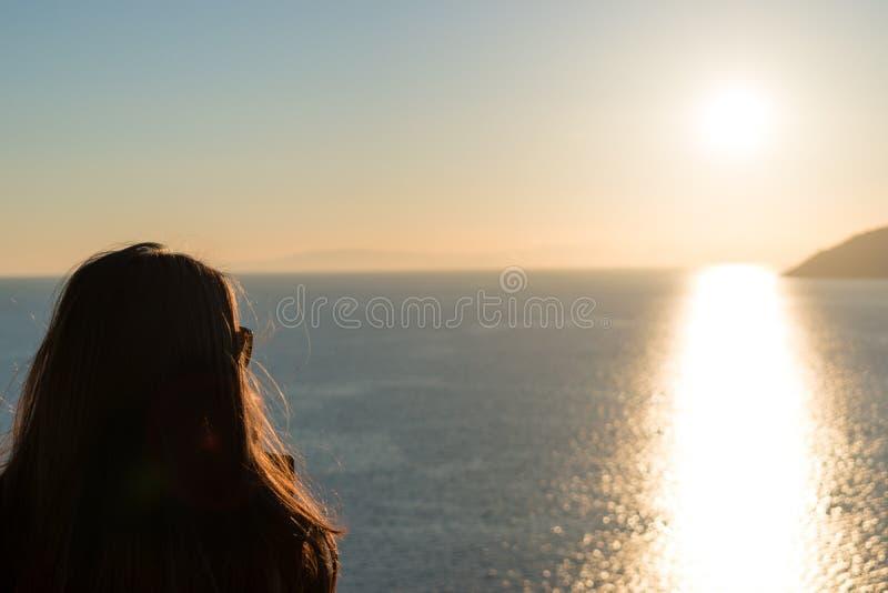 Het silhouet van vrouw let op zonsondergang over het overzees royalty-vrije stock afbeelding