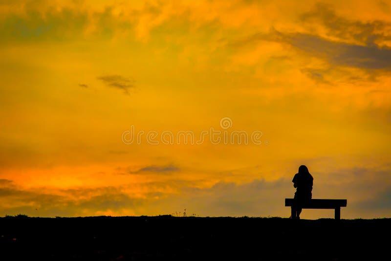Het silhouet van vrouw ontspant op zonsondergang van de stoel de gelukkige tijd royalty-vrije stock foto