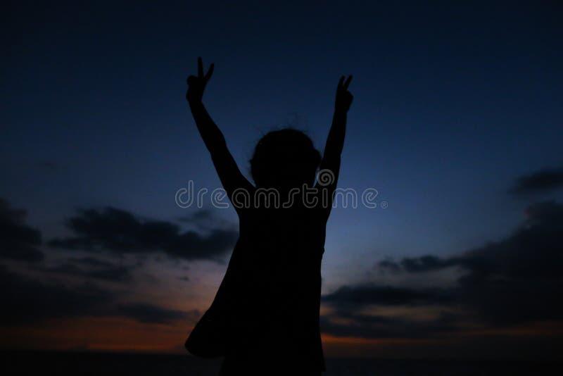 Het silhouet van weinig vrouwelijk kind met uitgestrekt dient de achtergrond van de zonsonderganghemel in royalty-vrije stock foto's