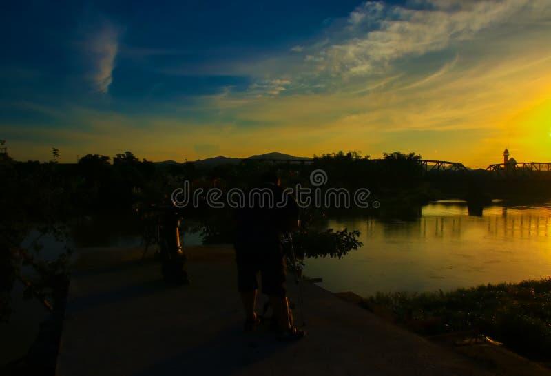 Het silhouet van zwaarlijvige mannelijke fotograaf die beeld in zonsopgang de ochtend met exemplaarruimte nemen voegt tekst toe stock foto