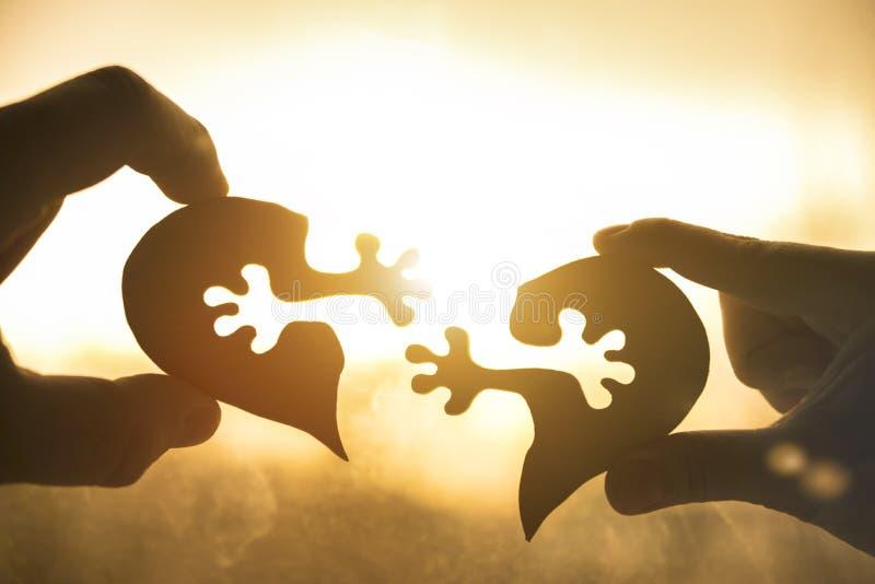 Het silhouet verbindt hart twee stukken van raadsel in handen van minnaars stock fotografie
