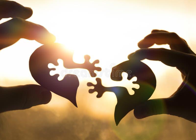 Het silhouet verbindt hart twee stukken van raadsel in handen van minnaars tegen royalty-vrije stock fotografie