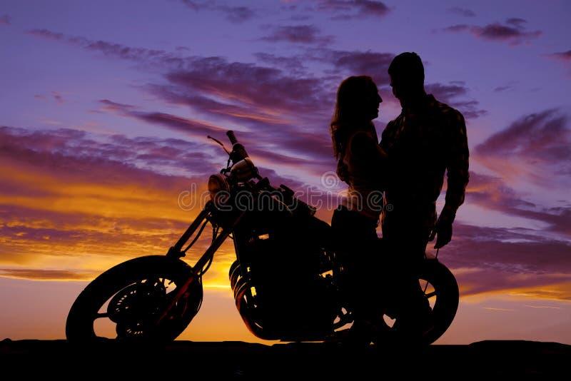 Het silhouetpaar bekijkt elkaar op motorfiets stock fotografie