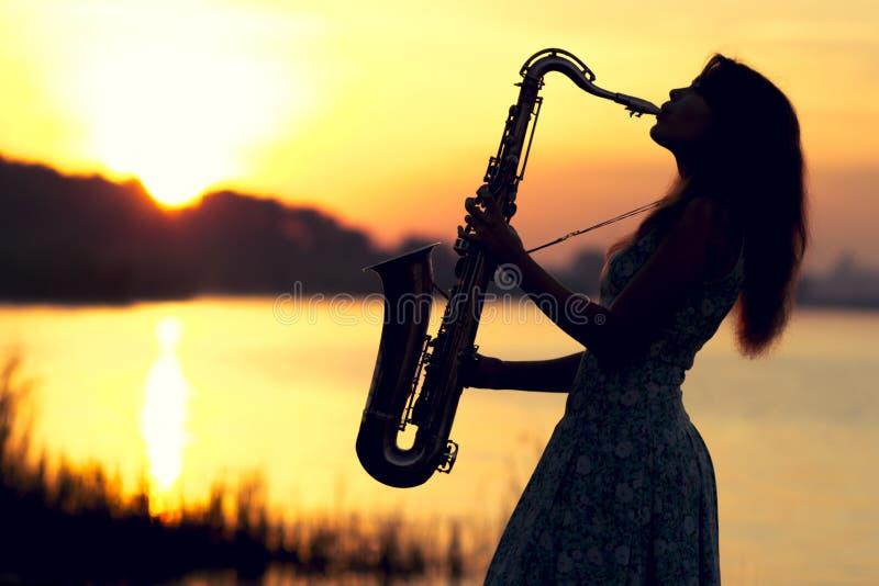 Het silhouetportret van een jonge vrouw die die skillfully de saxofoon in de aard spelen die haar vrede van kalmte geeft stock foto's
