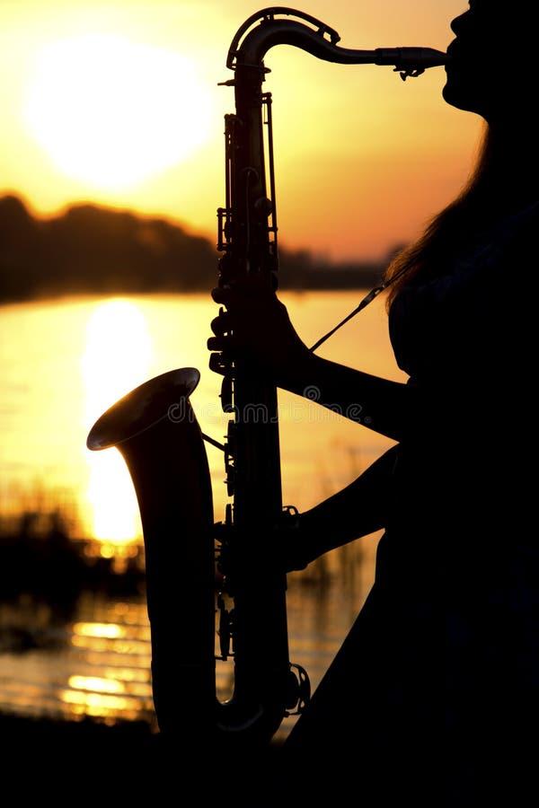 Het silhouetportret van een jonge vrouw die die skillfully de saxofoon in de aard spelen die haar vrede van kalmte geeft royalty-vrije stock fotografie