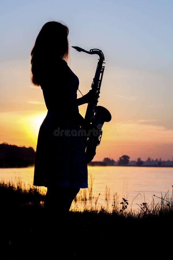 Het silhouetportret van een jonge vrouw die die skillfully de saxofoon in de aard spelen die haar vrede van kalmte geeft royalty-vrije stock foto's
