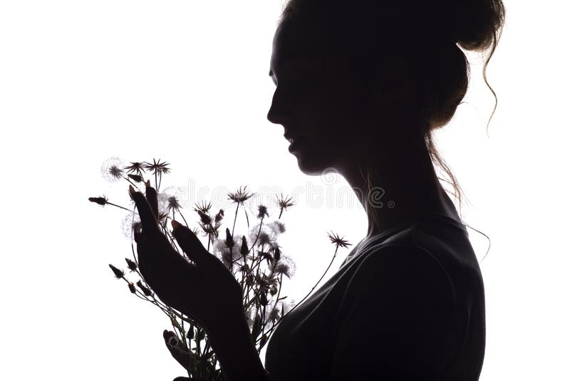 Het silhouetportret van een meisje met een boeket van droge bloemen, gezichtsprofiel van een dromerige jonge vrouw op een wit iso stock fotografie