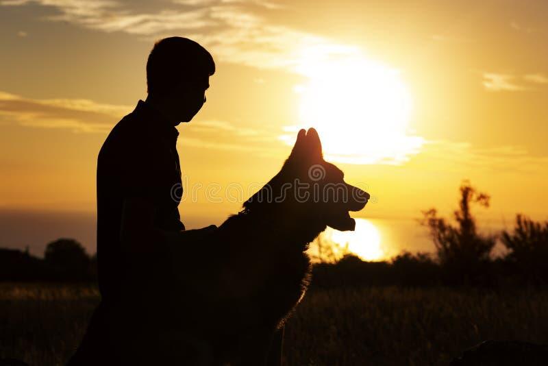 Het silhouetprofiel van een jonge mens met een hond die van mooie zonsondergang op een gebied genieten, jongen strelt zijn favori stock afbeelding