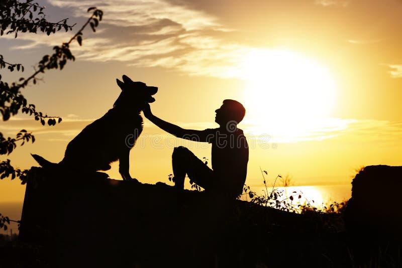 Het silhouetprofiel van mens en hondzitting voor elkaar op aard, jongen streelt zijn huisdier bij zonsondergang op een gebied, co royalty-vrije stock afbeeldingen