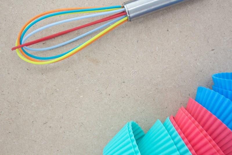 Het silicone zwaait en het kleurrijke geassorteerde cupcake silicone vormt kartonachtergrond royalty-vrije stock afbeelding