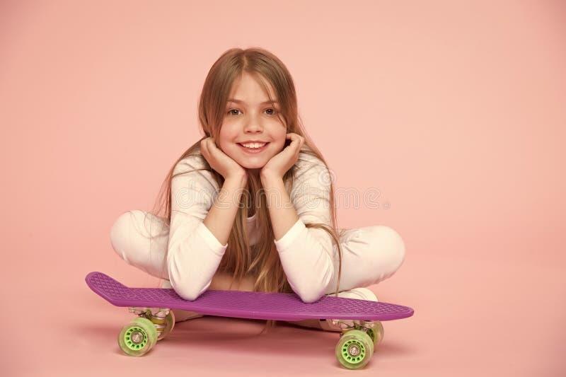 Het skateboardjonge geitje ligt op vloer op roze achtergrond Kindschaatser die met longboard glimlachen Kleine meisjesglimlach me royalty-vrije stock afbeeldingen