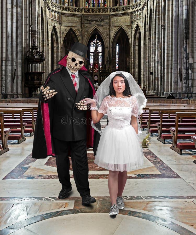 Het skelet als bruidegom houdt hand zijn bruid stock foto