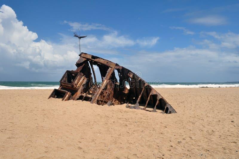 het skelet van het bootschip grunge in bruin zand in La Pedrera, Rocha, Uruguay half wordt begraven dat royalty-vrije stock afbeelding