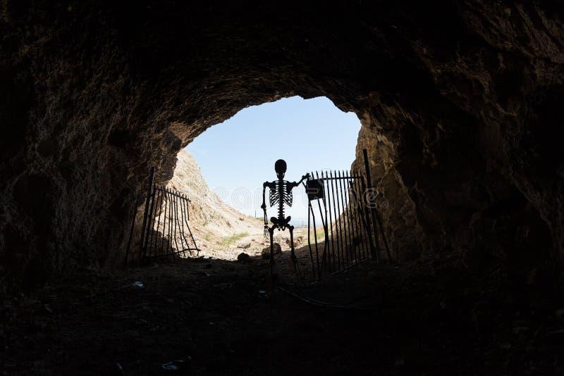Het skeletsilhouet in de mond van een mijnverblijf met poorten blijft uit levend stock foto