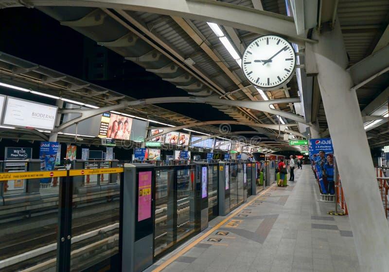 Het Skytrainstation tweezijdige klok tonen en een lang platform die met pijlen ondertekenen in-uit richting aan het vervoer royalty-vrije stock fotografie