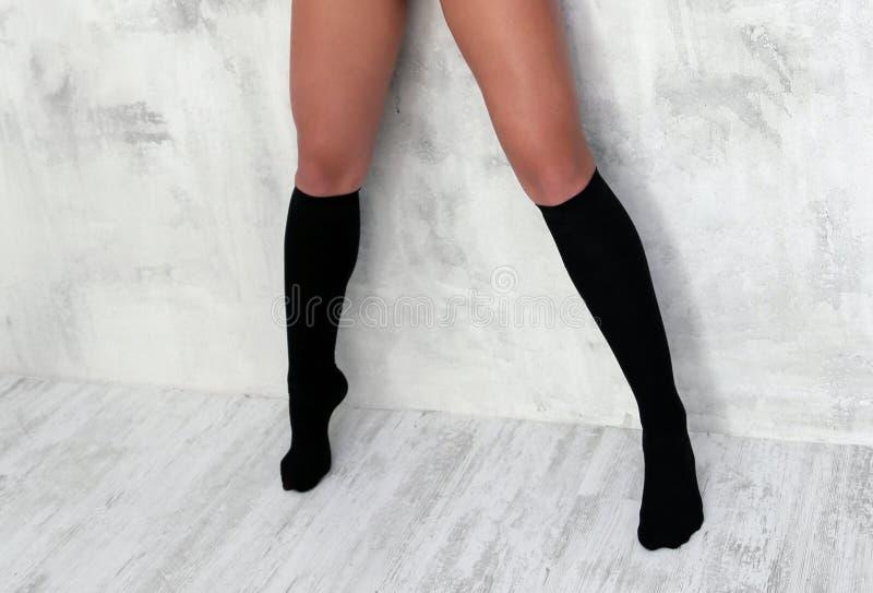 Het slanke atletische spier mooie lichaam van vrouwen Foto op witte achtergrond Een meisje met gelooide benen in sokken royalty-vrije stock afbeeldingen