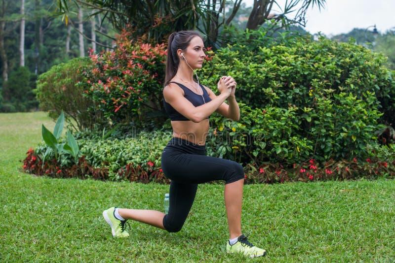Het slanke atletische vrouw uitwerken in park die knie-sprong oefening doen of valt uit stock fotografie