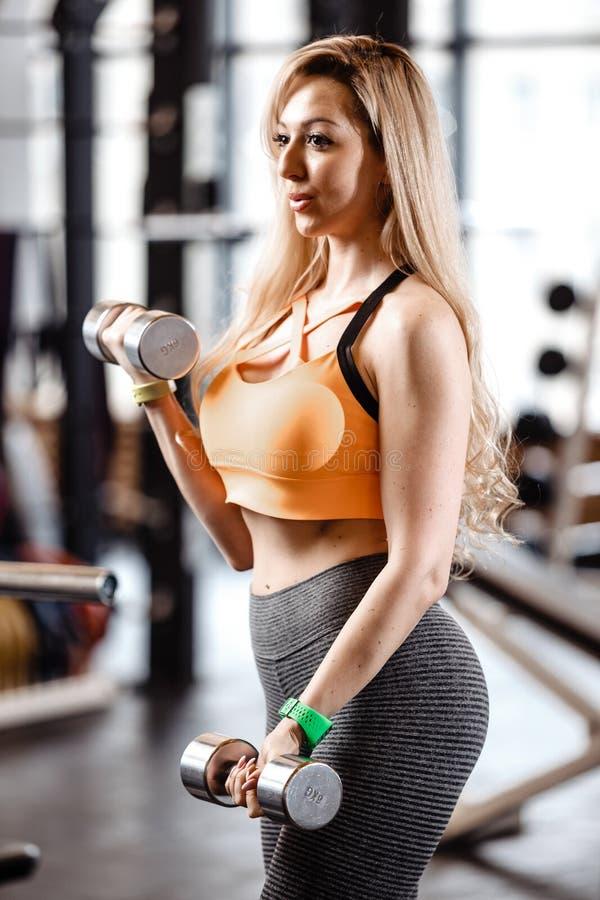 Het slanke blonde meisje met lang haar gekleed in een sportkleding doet oefeningen met domoren in de moderne gymnastiek met groot royalty-vrije stock afbeelding