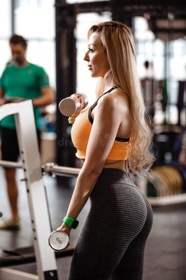 Het slanke blonde meisje met lang haar gekleed in een sportkleding doet oefeningen met domoren in de moderne gymnastiek met groot stock foto's