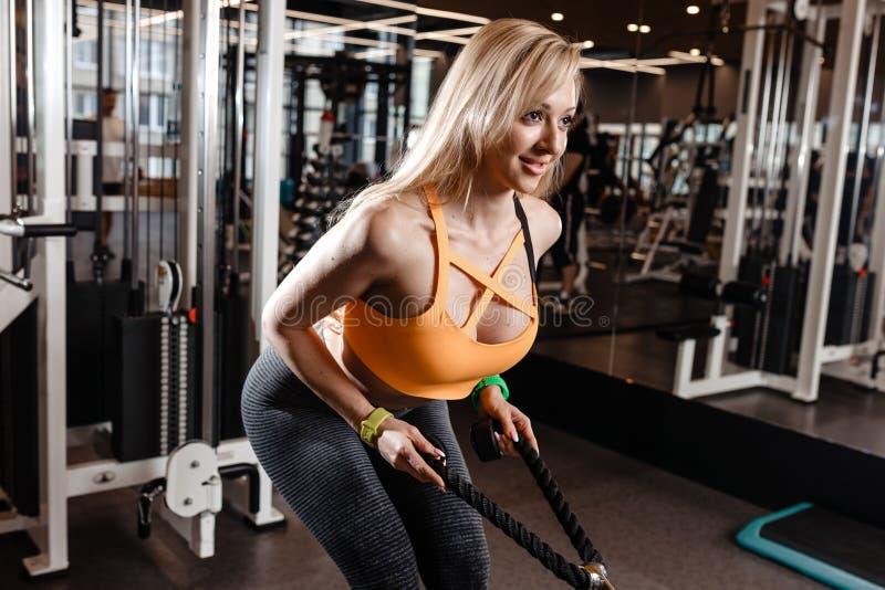 Het slanke blonde meisje met lang haar heeft een TRX-training in het moderne gymnastiekhoogtepunt van zonlicht royalty-vrije stock foto