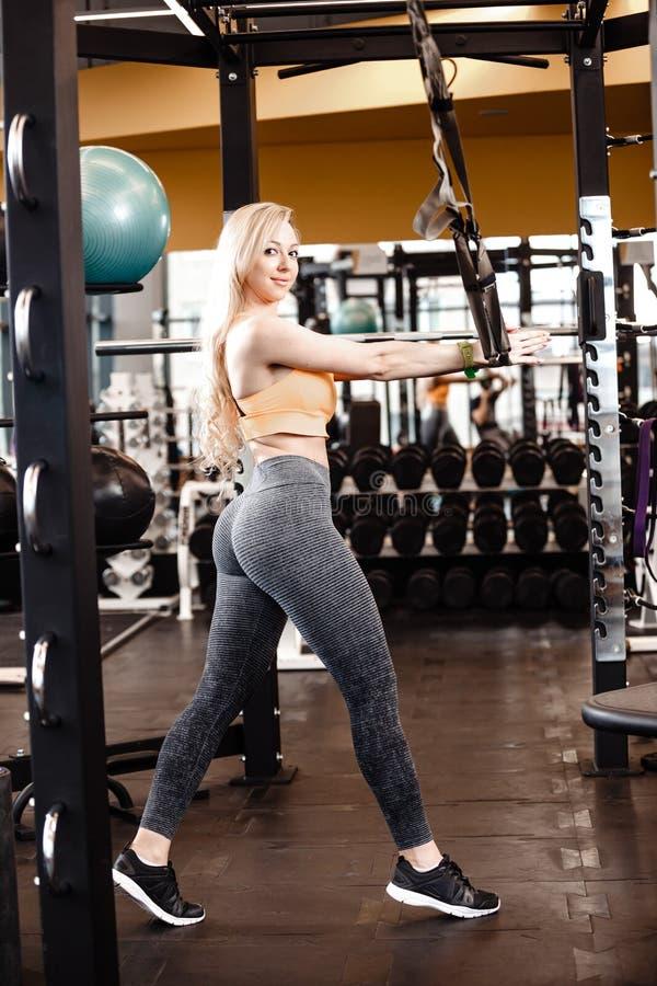 Het slanke blonde meisje met lang haar heeft een TRX-training in het moderne gymnastiekhoogtepunt van zonlicht stock fotografie