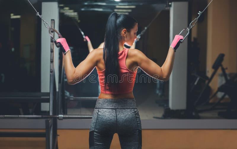Het slanke, bodybuildermeisje, doet de oefeningen die zich voor de spiegel in de gymnastiek bevinden royalty-vrije stock afbeeldingen