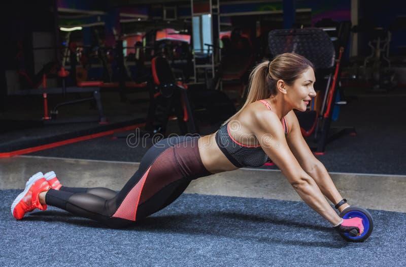 Het slanke, bodybuildermeisje, doet de oefeningen met Ab-Wiel in de gymnastiek stock afbeeldingen