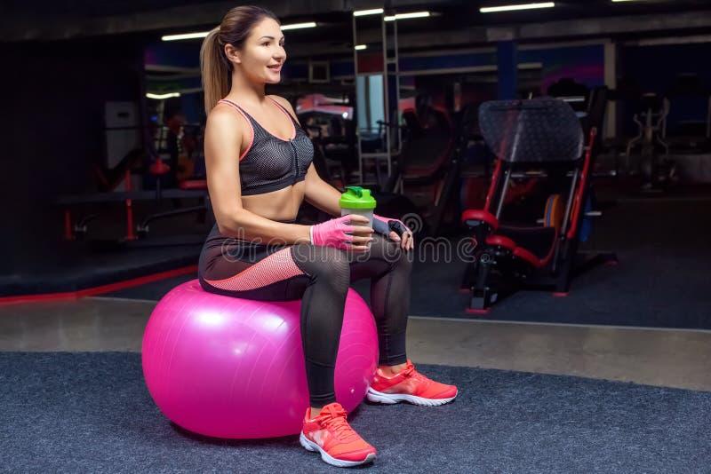 Het slanke, bodybuildermeisje, doet de oefeningen met geschiktheidsbal in de gymnastiek stock afbeelding
