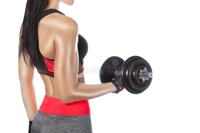 Het slanke bodybuildermeisje heft zware domoor op terwijl opleiding in de gymnastiek stock fotografie