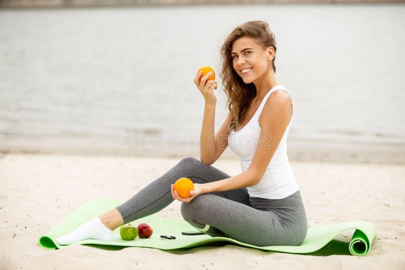 Het slanke donkerbruine meisje houdt vruchten in haar handen die op een yogamat situeren op zandig op een warme winderige dag stock afbeelding