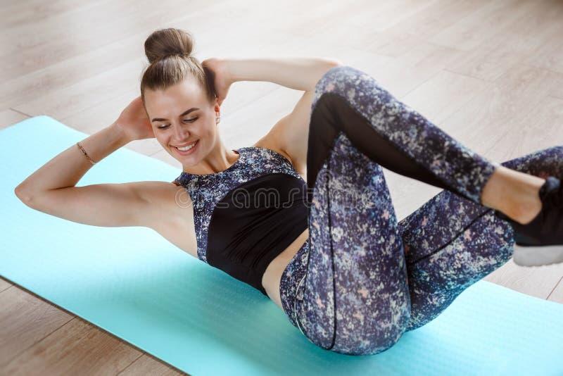 Het slanke geschiktheidsmodel oefent op de vloer op een groene yogamat uit stock foto