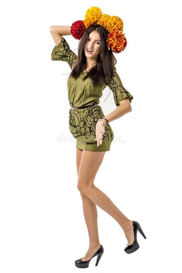 Het slanke jonge vrolijke meisjes bruine haar danst met een boeket van kleurrijke bloemen op haar hoofd royalty-vrije stock fotografie
