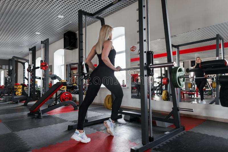 Het slanke jonge vrouwenblonde in een modieuze sportent-shirt in zwarte beenkappen in witte tennisschoenen behandelt fitness in d royalty-vrije stock afbeeldingen